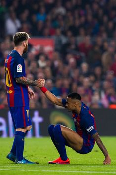 Lionel Messi (L) of FC Barcelona helps his teammate Neymar Santos Jr during the La Liga match between FC Barcelona and Granada CF at Camp Nou stadium on October 29, 2016 in Barcelona, Catalonia.