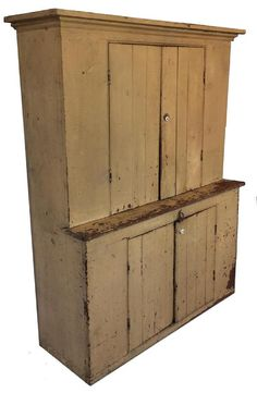 A228 Late 19th century Maryland Stepback Cupboard, with original mustard paint, unusual wide form, The top of the cupboard has simple cove molding, with two baton door over two door in the bottom. The wood is pine, circa