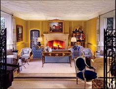 """""""It takes so much sophistication to use a simple fabric, like cotton,"""" says Marino, who designed a radiant yellow print, bordered with silk, for the living room walls. On the mantelpiece is a painting by John Wooton. The 18th-century bureau plat is by Etienne Levasseur   archdigest.com"""