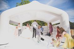 Let loose in a bounce house.   27 Impossibly Fun Ways To Entertain Kids At Your Wedding