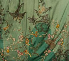 Detail /  BEADED and EMBROIDERED SILK EVENING CAPE, 1920's. Two shades of green satin embroidered in pastel silk and chenille, with gold metallic threads, having bronze seed and crystal bugle beads and sequins in an undulating pattern of swallows, flowers and butterflies, with panne velvet lining and ruched collar.