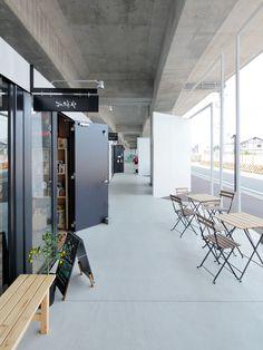 all photos(C)鈴木竜馬 リライトデベロップメントによる、東京都小金井市の「中央線高架下プロジェクト コミュニティステーション東小金井/モビリティステーション東小金井」です。 中央線高架化事業に伴って、新たに生まれた高架下スペースを有効活用するプロジェクト。沿線価値を向上させる取り組みの一環として企画され、地域周辺で活動する牽引役を巻き込むコミュニティプレイスとして計画した。建築設計のみならず、コンセプト立案、事業計画、リーシング支援、施設運営などを受託し、総合的にプロジェクトへ関わっている。 飲食店や物販店の他にイベントスペース、広場など、様々な使われ方を許容する多様な場を用意し、地域に開かれた施設となることを期待している。高架下全体を一体感のある室内のような空間とするために、道路境界に大きなフレームと壁面を配し、130mの仮想的な立面をつくり出した。この障子と枠とで構成される、建具の形式を拡大解釈したような厚みのないファサードにより、空間に「入る」という行為を顕在化させ、商業施設のエントランスのあり方を更新することを試みている。…
