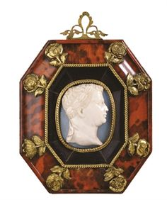 A CARVED OVAL ONYX CAMEO BUST OF THE EMPEROR CLAUDIUS 17TH CENTURY Wreathed and facing in profile to the right; in a silver-gilt rope-twist oval mount applied to a later octagonal ebony and tortoiseshell frame embellished with eight silver-gilt roses, suspension loop above.