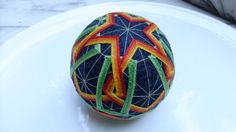 Handmade Japanese Temari Ball with circumference of 25.5 cm / 10.03  Colors: green, black, orange, gold  Seen among other balls in two of the images