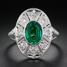 Art Deco emerald, platinum and diamond ring. A richly saturated, deep green emerald, weighing 1.25 carat, is intriguingly cut with an oval outline and an octagonal step-cut faceting. This gorgeous bezel-set gemstone is set in platinum in the center of a radiating diamond-set frame, enhanced with decorative open-work and finely milgrained edges. The top of the ring shank is adorned with neo-classically inspired hand engraving and the under gallery is imbued with an open scalloped motif.