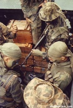 SEAL team members wearing a variety of camouflage clothing check their weapons as they prepare to conduct an operation from a riverine craft. October 1968 - The National Archives ~ Vietnam War