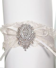 Created with cascades of Swarovski crystals, this garter will catch the light beautifully, so don't be afraid to flash some leg!• Swarovski crystal brooch• Stretch elastic with heart detailing• Swiss satin bow• One size fits most• Available in ivory or white laceNeed help with sizing