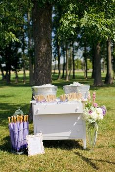 Lavender wedding ceremony decor. Refreshing  table with fans, umbrellas and water for outdoor wedding