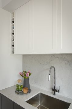 Luxe contemporary kitchen with hidden butler's pantry featuring white Shaker cabinetry from Freedom Kitchens.  Island benchtop and splashback by Caesarstone in Noble Grey.  By winners Josh & Elyse.