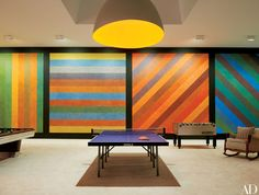 The homeowners installed a Sol LeWitt wall drawing in the structure, which also features an Ingo Maurer ceiling light and various games tables.