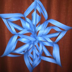 Decorative Christmas snowflake or just for fun paper craft decor. Made with colored construction paper, tape and staples. (Made by my 9 year old son)