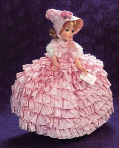 """""""Goya"""" Portrait Doll,1968 21"""" (53 cm.) Vinyl socket head,adult-lady shaped torso,jointing at shoulders,hips and knees,high-heel posed feet,blonde hair in ornate fashion,sleep eyes with very long lashes. Costume: pink taffeta gown with eight tiers of skirt ruffles,lacy tiered pouf sleeves,pink taffeta """"beehive"""" bonnet with floral trim and pink streamers,pink taffeta frou-frou petticoat,panties,stockings,coral satin heels,solitaire. The costume is labeled Alexander,and the doll has her…"""
