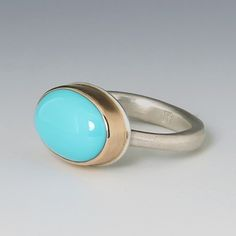A Jamie Joseph sterling silver and 14K yellow gold ring with a smooth oval Sleeping Beauty turquoise on an egyptian band.