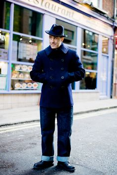 """Christos, has a hat that is from Lock St James of London, the coat is a 10 button 1940′s navy pea-coat (quite rare). The jeans are Levis 501 xx, teamed with a French Navy sweater and shoes are Redwing. Christos -""""My absolute favourite trend is mid 20th century, 40′s or 50′s. I take my inspiration from the stars of the 1940′s and 50′s – they were great role models and I loved their masculinity. My least favourite trend is 80′s high street fashion and large people squeezing into skinny jeans."""""""
