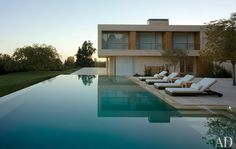 Chaise longues and side tables by Christian Liaigre populate a deck overlooking the infinity-edge pool.