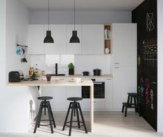 cuisine blanc laqué en noir et blanc avec facade cuisine blanche et petit bar en bois avec tabourets noirs, suspensions noires et mur repeint de peinture ardoise