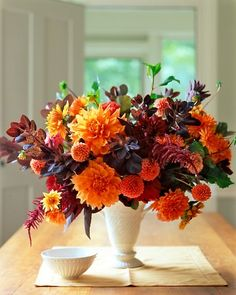 A china vase holds 'Ben Huston,' 'Old Gold,' 'Anries' Orange,' 'Prince Noir,' and 'Jomanda' dahlias