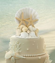 """This resin seashell caketop makes the perfect decoration for destination or beach-themed weddings. Size: 4"""" wide, 5"""" tall."""