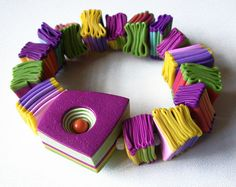 by Natalia G. de Leaniz.  Love the folded clay, so informal, mixed with the precisely shaped focal bead.