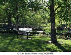 A shaded park bench offers a peaceful view of trees, flowers, and wooden bridges over a stream.