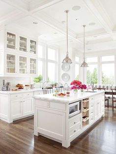 bright white kitchen with island and dining nook love the glass front cabinets and vintage style pendant lamps, some blue would be nice too for a vintage look x