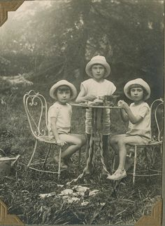 Three children having an outdoor tea party - it occurred to me that they are possibly triplets. What do you think.