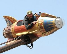 Coldplay's Chris Martin rides a rocket ship with his son Moses in Disneyland on April 3, 2009.