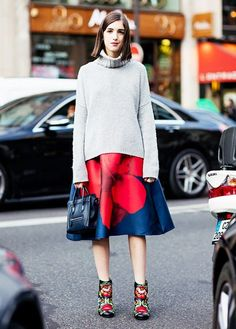 A turtleneck sweater is paired with a printed knee-length skirt, floral boots, and a mini Céline tote bag