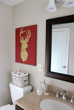 Here's a quick and easy holiday DIY project. Take a canvas, wrap it in plaid fabric, and create a reindeer silhouette with gold glitter.