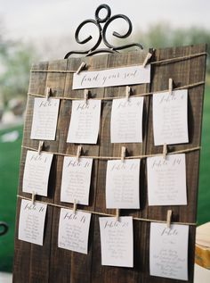 Trilogy at Vistancia Wedding | A wooden guest seating chart with calligraphy writing on paper strung by clothespins along a string | www.weddingsatvistancia.com | Leslie D. Photography