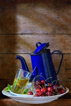 http://nikolay-panov.artistwebsites.com/products/pear-and-apricots-nikolay-panov-art-print.html • Fruits still life with blue teapot and glass of green tea balancing with cherries on wooden background lighted by daylight in country house on sunny day in summer