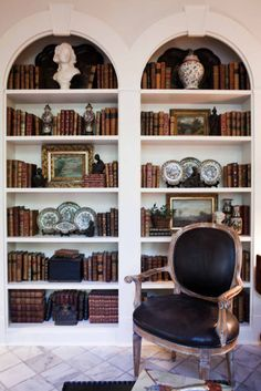bookcases filled with decor and having arched tops, only thing that could be prettier would be to have those keystones  engraved with the letter of the alphabet that the books on the shelves correspond to.