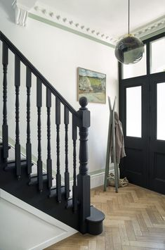paint and paper library monochrome. Contemporary hallway design with black stairs and white walls.