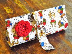 Carteira em cartonagem, estruturada, revestida com tecido importado 100% algodão, linha Loralie.  Aplicação de flor em crochê. Fecho de pressão e argolas. R$ 80,00