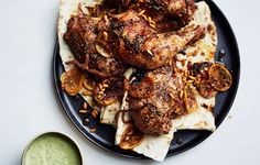 Za'atar Roast Chicken with Green Tahini Sauce  Because of the brothy marinade, the skin won't get as crisp as with other roast chickens, but the flesh will be so tender, you'll want to eat it with your hands.