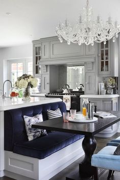 Gray kitchen, tufted dining banquette, chandelier, range hood | Oliver Burns