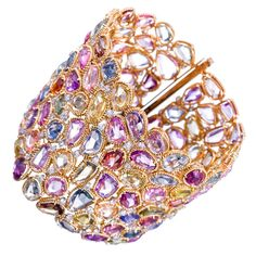 Presented as a mosaic of minimally faceted sapphires, each in its own twisted golden bezel and peppered with brilliant diamonds at random intersections. The colors are a range of soft blues, pinks, purples, greens, yellows and oranges. In total, 132.16 carats of sapphires and 3.99 carats of diamonds are paved together to create a carpet of gemstones to adorn your wrist.  7.25 inches long by 2.25 inches.