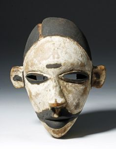 "Nigeria, Ogoni peoples, ca. early 20th century CE. This is a small cane wood dance mask. The face has narrow slits for eyes, serious lips, and pronounced ears and nose. There are marks of scarification/tattooing on the forehead and extending out from the mouth. The white face paint marks this mask as an ""elu"", a spirit. The Ogoni encountered European colonists quite late - 1901 was the year they encountered the British - so their artistic tradition retains many pre-colonial elements compared…"