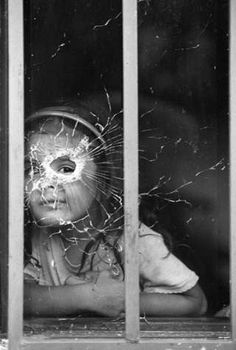 Girl looking through bullet-shattered window