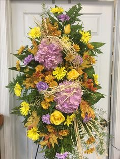 Fall sympathy standing spray by Hartman's Flowers. Funeral arrangements and flowers.