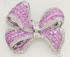 Pink Sapphire, Diamond and 18K White Gold Bow Brooch  The ribbon bow decorated with invisibly-set pink (diffusion treated) sapphires and round diamond trim, gathered by a princess-cut diamond channel.  Image www.dupuis.ca/