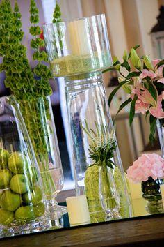 Detalle  De la decoración floral.   Los centros de flores fuera de dos tipos: centros bajos con rosas, lilium, lisianthus, anastacia verde, hortensias, peonías, todas ellas en tonos rosa claro, acompañados con velas, y centros altos en copas martini, con el mismo tipo de decoración.