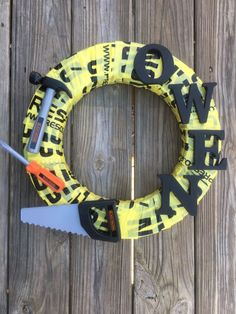 """Having a construction party for your little boy or a special guy in your life? This wreath is perfect for the party! It is made from a 16"""" foam wreath wrapped in caution tape with Black and Decker too"""