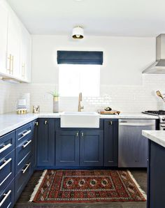kitchen trends navy cabinets on the bottom, white counters, backsplash, and uppers.