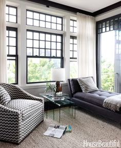 In a window-filled corner, a swivel chair is covered in Studio Bon's RicRac, and a chaise provides seating without blocking views. Glass nesting tables from Hinson.   - HouseBeautiful.com