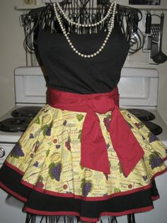 Ladies Wine Fancy Hostess Half Apron  This aprons has two circle skirts, the bottom is solid black and the top has a cork color background with bunches of grapes and wine bottle labels all over. Both skirts are finished with hand made wine color bias tape to match the pocket under the top layer (shown in photo #2), waist band and ties.  tutu is not included, for display purpose only  One size fits most  Machine wash, tumble dry med, no chlorine bleach  This apron is ready to ship and comes…