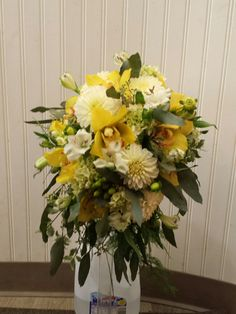 Yellow and white Cascade featuring, white dahlias, gold cymbidium orchids and hypericum berries #gouldsflowers #716433ROSE #gouldsflowers&gifts www.gouldsflowers.com