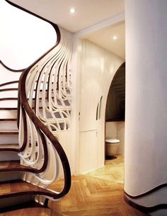 The sculptured staircase, designed by alex haw's london-based atmos studio for a residential project,  recreates the structural flow of the living spaces, incorporating the pattern of the house's skirting board into its form.   in accordance with the greater layout of the space, which seeks to visually connect rooms and other living spaces,  the risers of the staircase extend into the bathroom space below, stretching along the wall and around existing furniture,  to integrate fully into the…