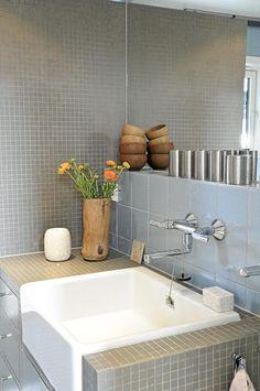 Badet er dekorert i dempede farger med fliser fra den nederlandske produsenten Royal Mosa. Den firkantede vasken er dekket av fliser. Treboller og blomster i en trevase bryter opp det gjennomgående grå badet.