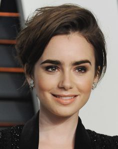 """The British actress (and daughter of singing legend Phil Collins) debuted a cool crop at the Vanity Fair Oscar Party. <span><a href=""""https://instagram.com/lilyjcollins/"""">Collins</a></span> shared the long-on-top short cut on her Instagram exclaiming, """"I chopped it!"""" along with the happy hashtag: #shortandlovingit. Keeping the layers longer in front gives her additional styling options."""